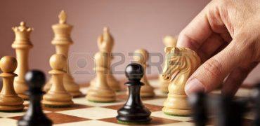 50131011-main-homme-d-placer-le-jeu-d-checs-chevalier-blanc-au-milieu-d-un-jeu-d-checs-attaquer-les-noirs